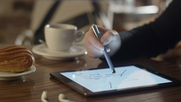Woman Drawing on Tablet PC in Coffee Shop 1