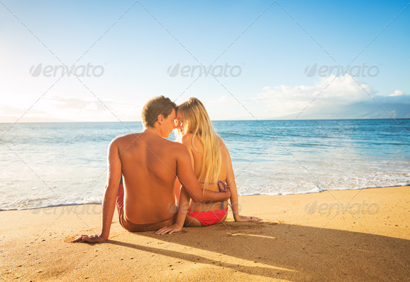 Couple Watching the Sunset on Tropical Beach Vacation - Stock Photo - Images