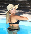 portrait the smart blonde in a hat in swimming pool - PhotoDune Item for Sale