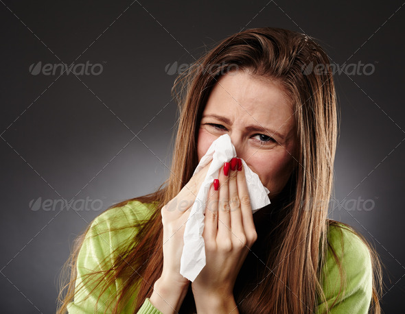 Caucasian female with flu blowing her nose - Stock Photo - Images