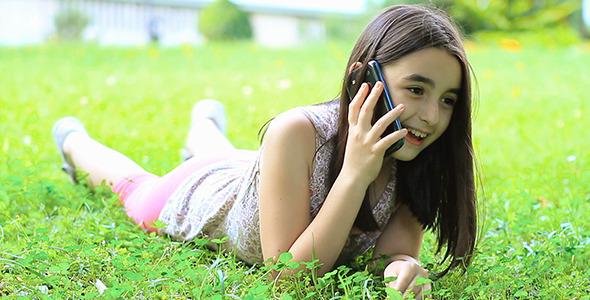Little Girl Talking on Smart Phone on Grass 1