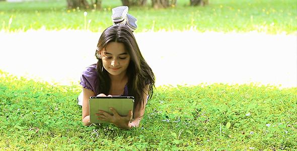 Teenage Girl Using Digital Tablet on Grass 2