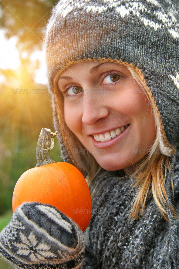 Pretty young woman holding a pumpkin - Stock Photo - Images