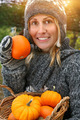 Pretty young woman holding basket of pumpkins - PhotoDune Item for Sale