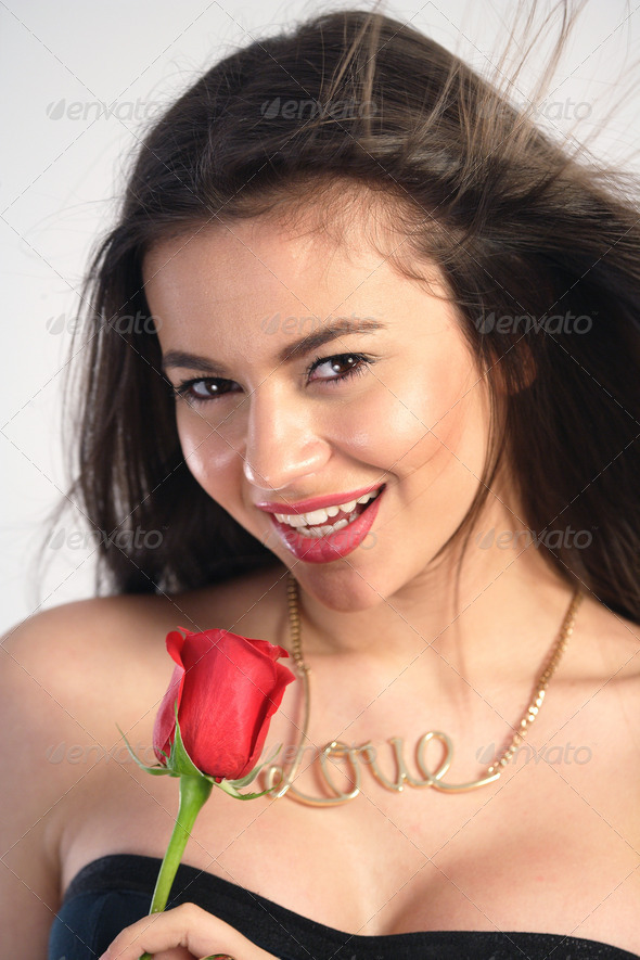 Young woman holding a red rose - Stock Photo - Images
