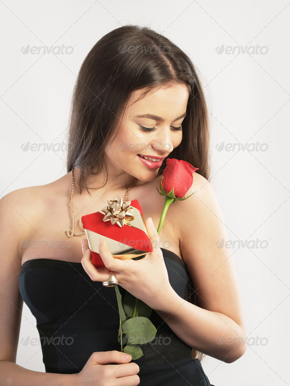 Young woman holding a gift and a flower - Stock Photo - Images