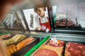 Saleswoman Looking At Variety Of Meat Displayed In Shop - PhotoDune Item for Sale