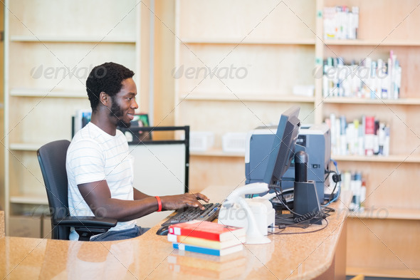 Side view of young librarian working on desktop PC at desk in library