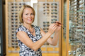 Woman Selecting Glasses At Optician Store - PhotoDune Item for Sale