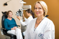Confident Eye Doctor With Colleague Examining Patient - PhotoDune Item for Sale