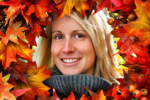 Woman looking through autumn leaves, smiling - Stock Photo - Images
