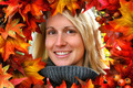 Woman looking through autumn leaves, smiling - PhotoDune Item for Sale
