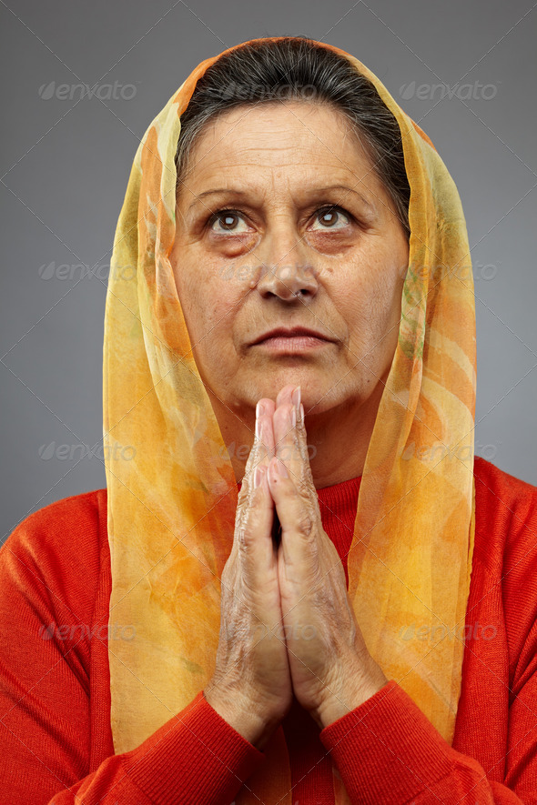 Old woman praying - Stock Photo - Images