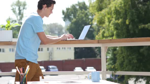 Download Sunny Day, Man Standing and Typing on Laptop in Balcony nulled download