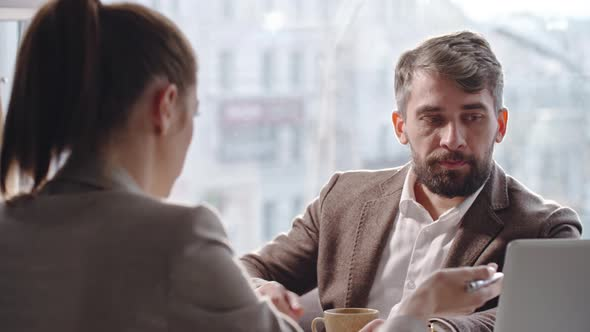 Businessman Listening to Colleague at Coffee Break