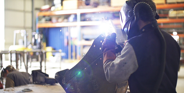 Man Welding On An Excavator Part