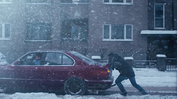 Man is Pushing Broken Down Car at Winter Time