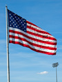 American Flag Waving Proudly on a Clear Windy Day at a Stadium - PhotoDune Item for Sale