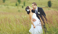 Young groom and bride at field.