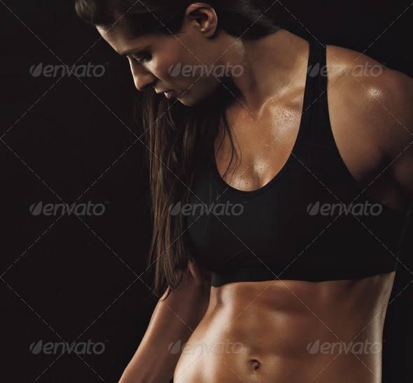 Image of fitness woman in sports clothing working out on black background. Young female with perfect muscular body.