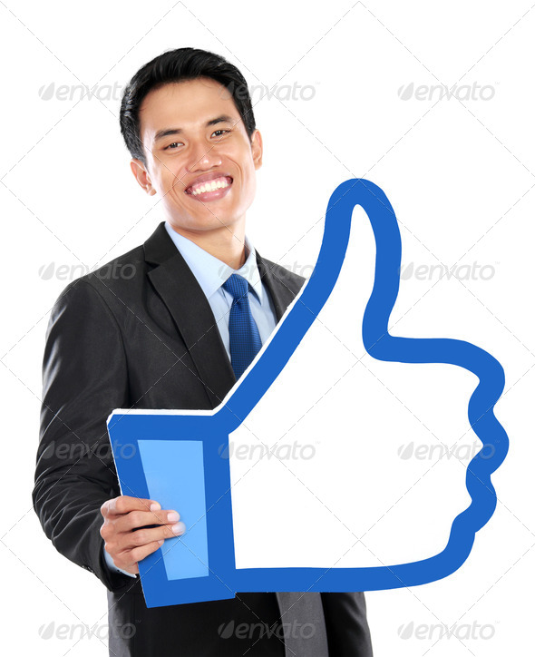 Portrait of businessman holding like sign - Stock Photo - Images