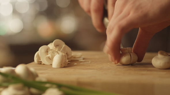 Chef is Rapidly Chopping Mushrooms in Kitchen