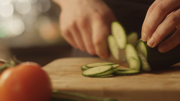 Chef is Rapidly Chopping Cucumber in Kitchen