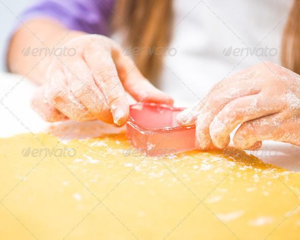 little girl cuts dough in the shape of heart