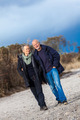 mature senior couple walking on the beach autumn winter - PhotoDune Item for Sale