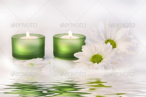 Green candles and daisies near water reflection - Stock Photo - Images