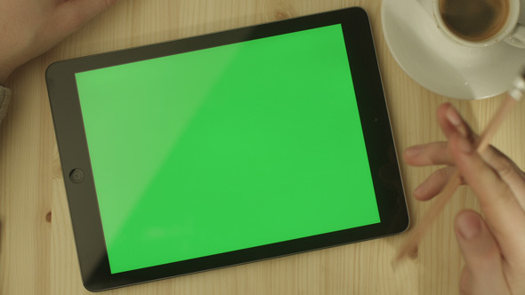 Tablet with Green Screen Laying on a Wooden Table