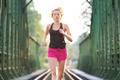Active female athlete running on railaway tracks.