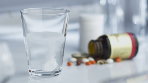 Tablet of Aspirin Dissolving in Glass of Water