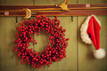 Red wreath with Santa hat hanging on rustic wall - PhotoDune Item for Sale