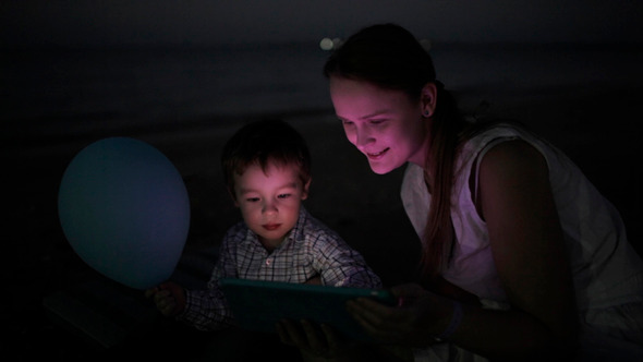 Kid With Mom on Beach At Night
