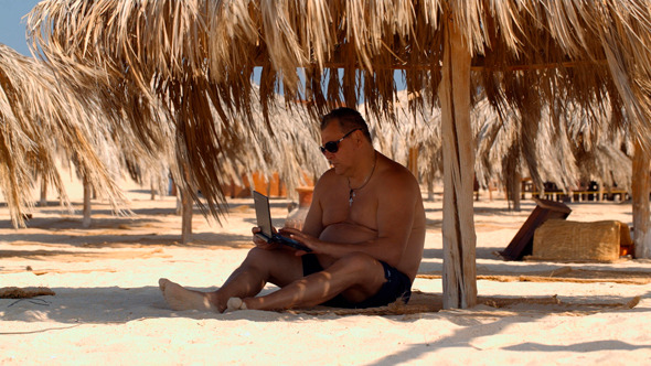 Relaxing on Beach With Laptop