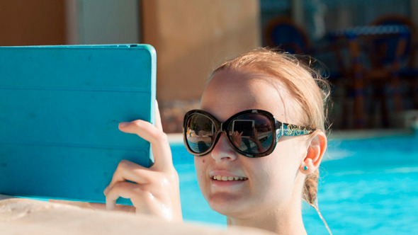 Young Woman Using A Tablet Poolside