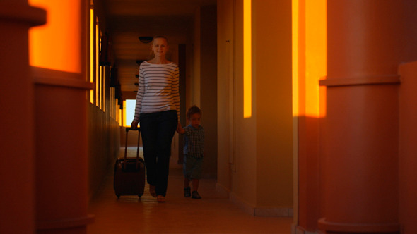 Mother And Son With Luggage in Hotel Corridor