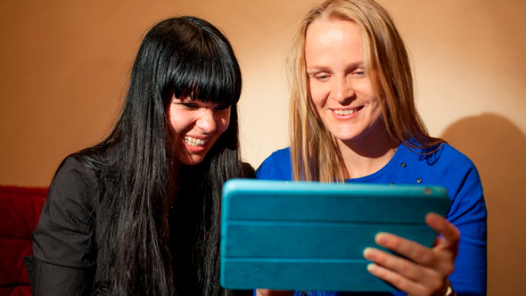 Two Young Woman Reading A Tablet-Pc