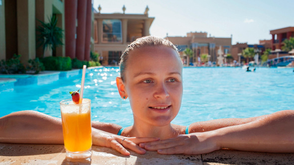 Woman in the Pool with Juice and Splashing Feet