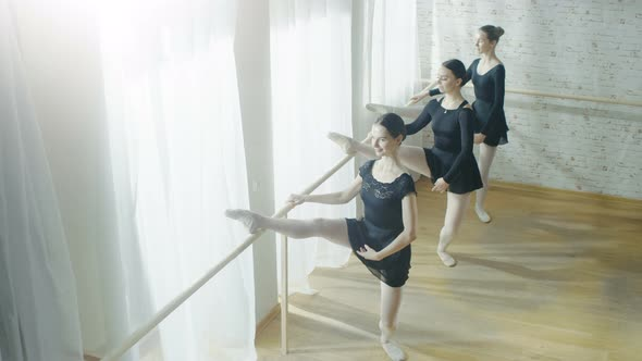 VideoHive Three Young and Graceful Ballerinas practice Stretching Legs on the Barre 19473647