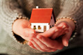 Woman holding a small new house in her hands. Real estate, mortgage - PhotoDune Item for Sale
