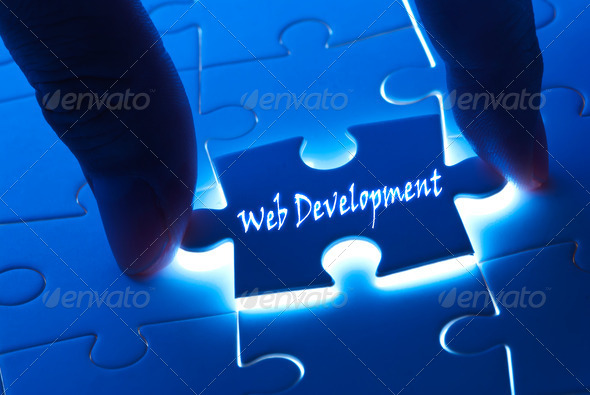 Web development on puzzle piece - Stock Photo - Images