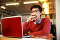 Handsome asian man working on laptop and drinking coffee