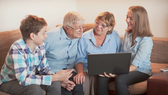 Teenager Explains How To Use a Laptop to an Elderly Person
