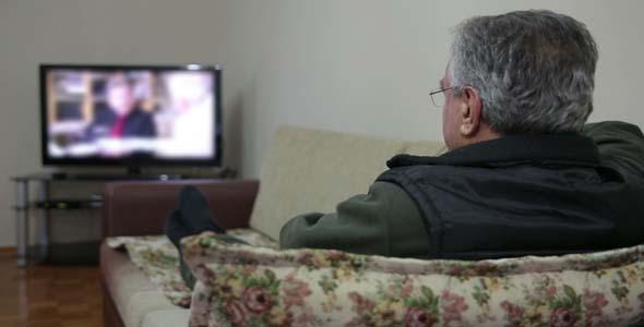 Senior Man Watching TV While Sitting On Sofa