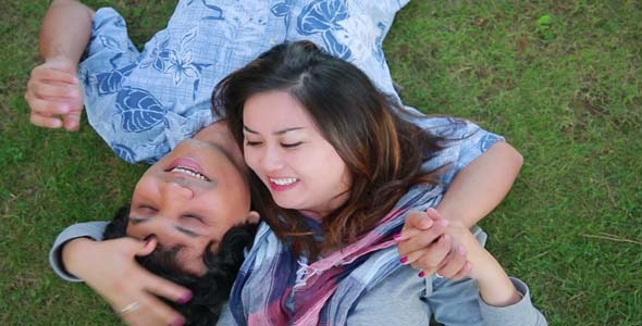 Young Couple Relaxing On Lawn In A City Park