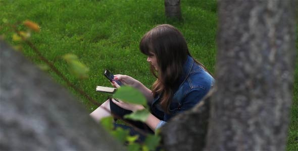 Girl With Mobile Phone In The Garden 1