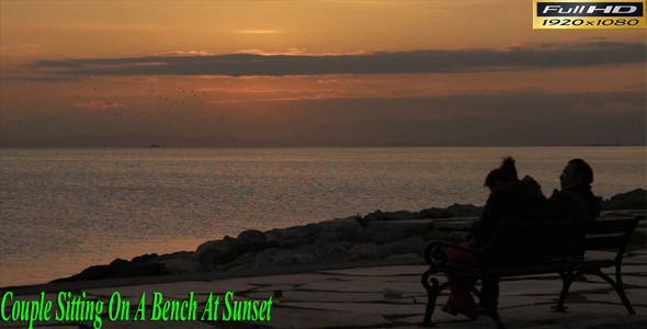 Couple Sitting On a Bench At Sunset