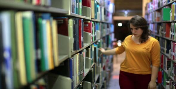 Female Student Wandering Between Shelves